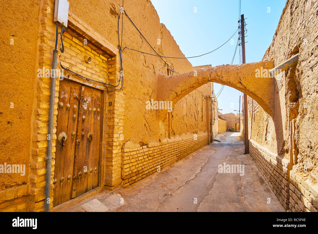 Die schäbige Straße der alten Stadt mit mittelalterlichen Holztür, bröckelt Adobe Wände, gebogene kuche Durchgang und enge Straße, Yazd, Iran. Stockfoto