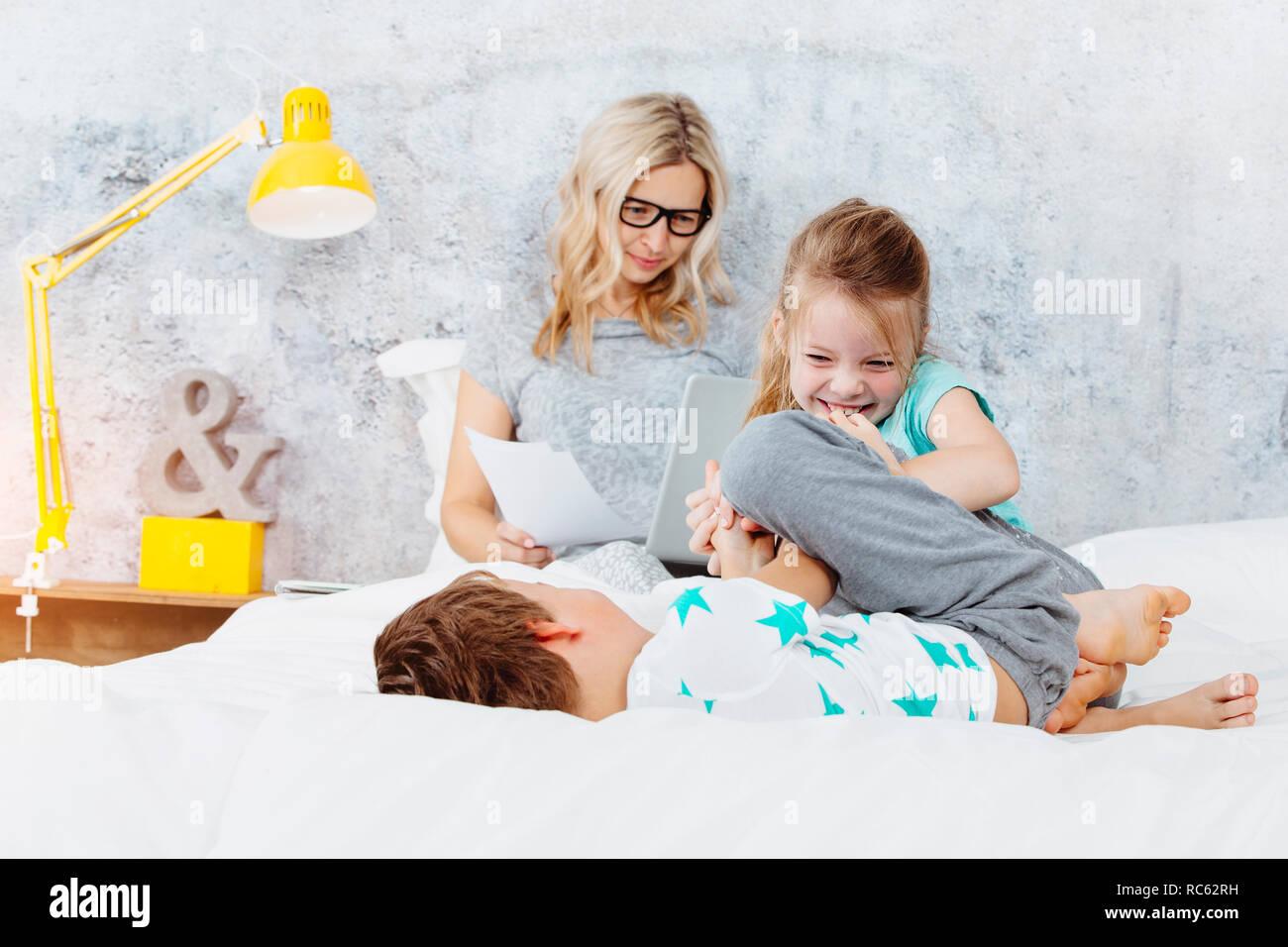 Happy business Mama auf der Arbeit während Ihre Kinder spielen im Bett Stockfoto