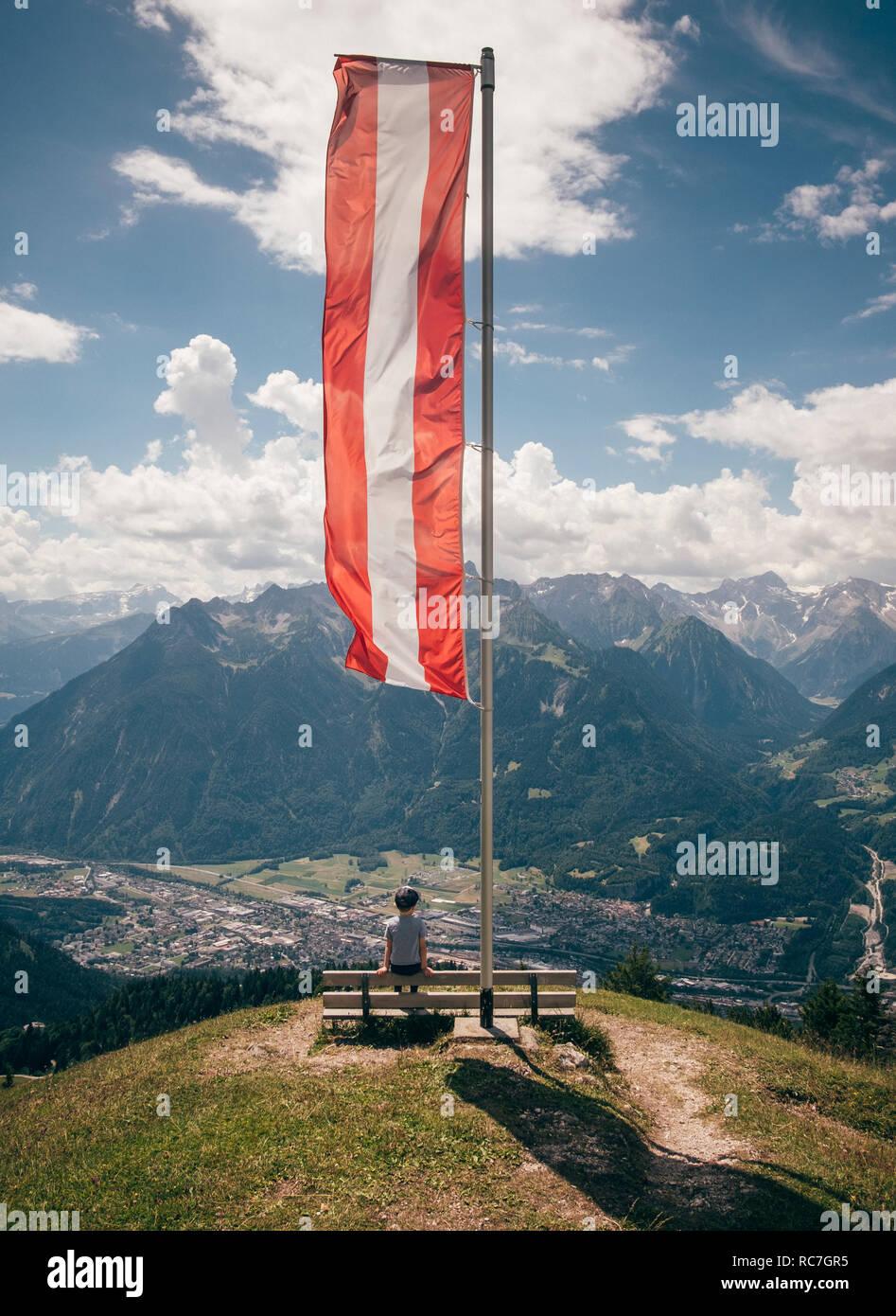 Junge sitzt unter österreichischer Flagge Betrachtung Berglandschaft, Bludenz, Vorarlberg, Österreich Stockfoto