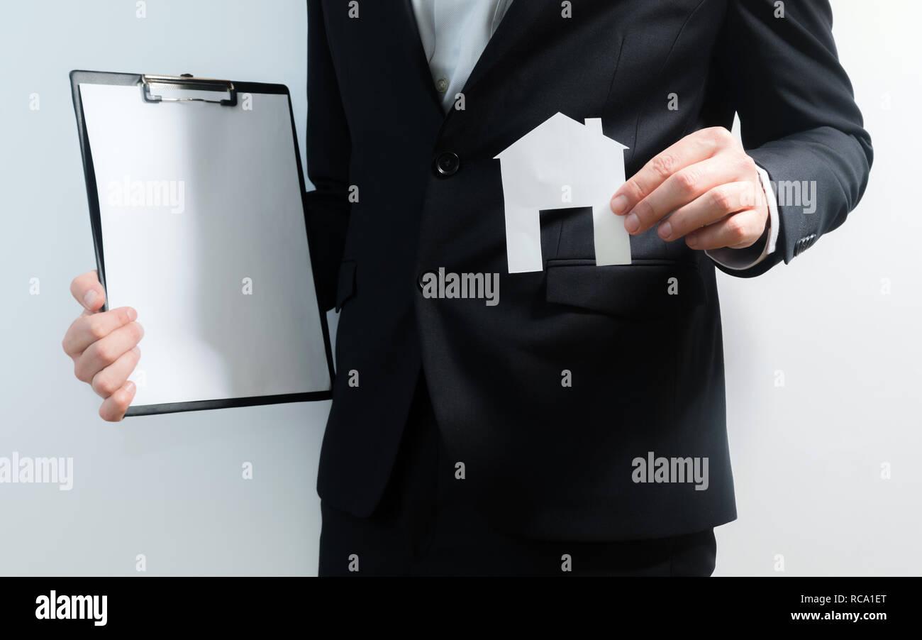 Realtor, real estate agent Holding Tablet und Papier Modell eines Hauses. Zugang zu Hause. Investitionen und Immobilienkauf Konzept Stockbild