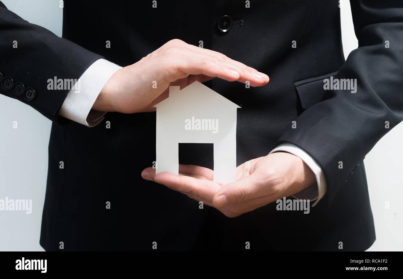 Realtor, real estate agent Holding Papier Modell eines Hauses. Zugang zu Hause. Investitionen und Immobilienkauf Konzept Stockbild