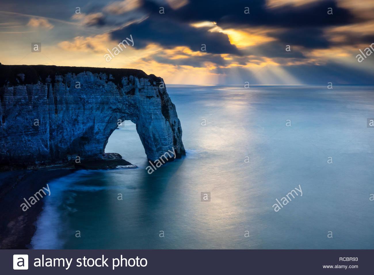 Sonnenstrahlen, auch als Gott strahlen bekannt, über den Atlantischen Ozean und ein großes Meer arch genannt Manneporte in den späten Nachmittag in Étretat, Franc form Stockbild
