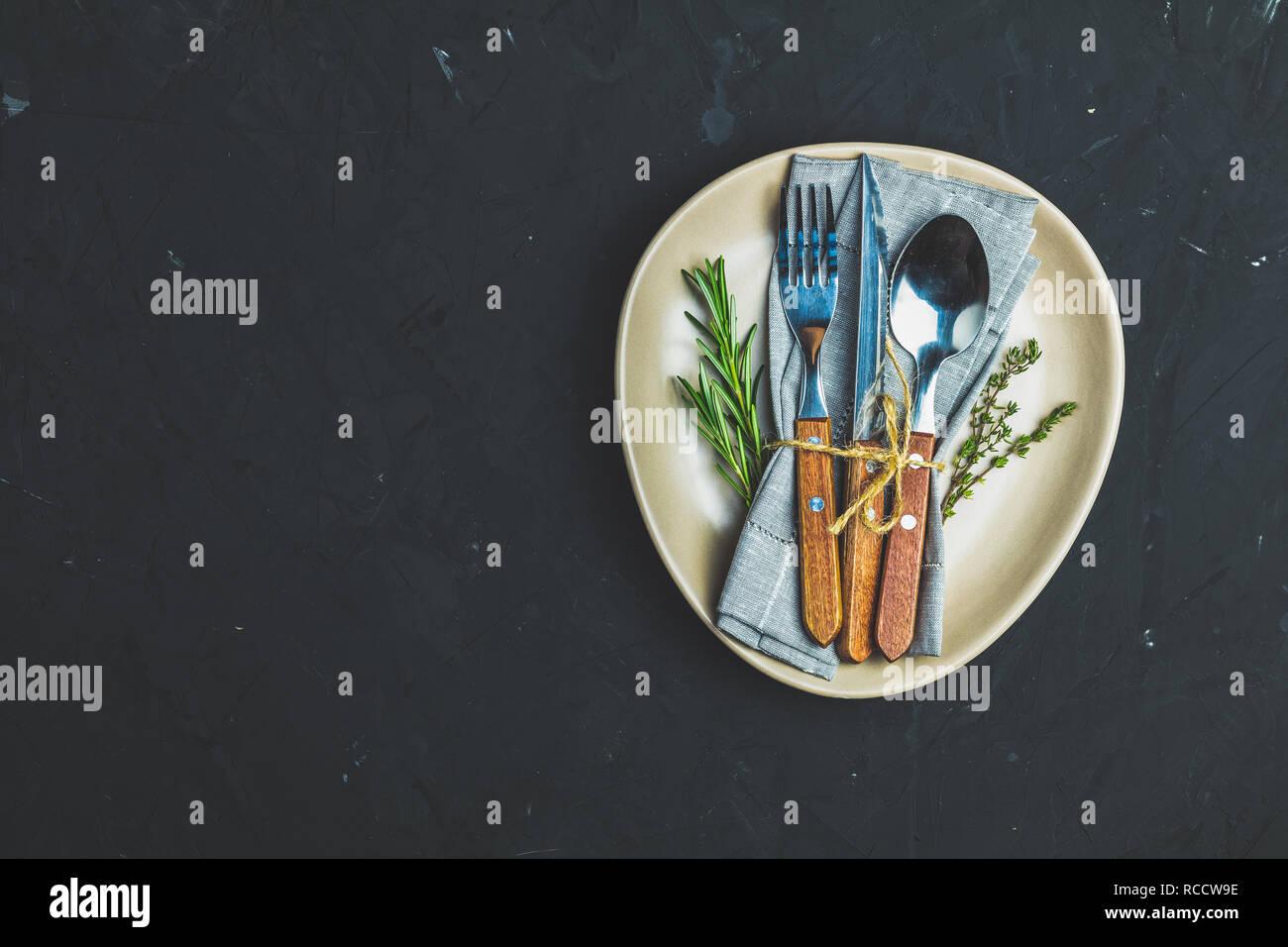 Rustikale vintage Set Besteck Messer, Gabel und Löffel in Licht Keramikplatte. Schwarzer Stein Betonoberfläche Hintergrund. Ansicht von oben, kopieren. Stockbild