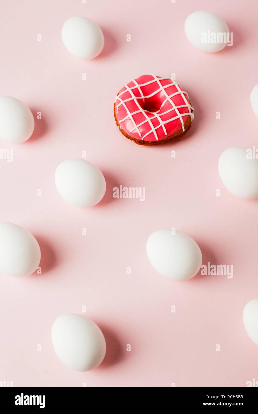 Ostern weiße Eier Wiederholung mit Schatten und rosa Donut auf Rosa pastell Hintergrund, Systemfehler, Kopie, trendige Hintergrund Stockbild