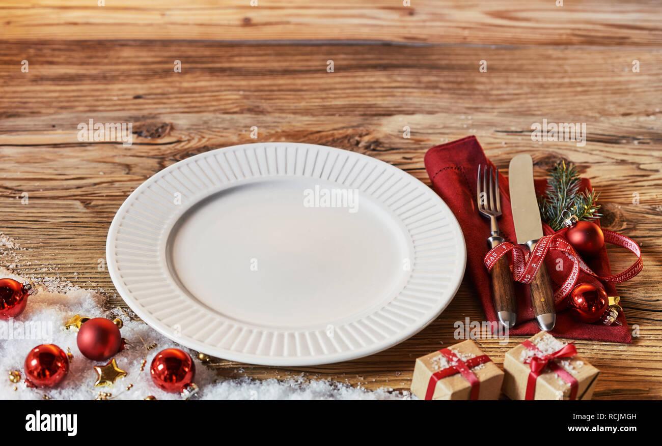 Geschmuckten Tisch Mit Einem Leeren Weissen Teller Durch Rote Themed Geschenke Dekoration Servietten Besteck Und Schnee Auf Einem Holz Tisch Umgeben Stockfotografie Alamy