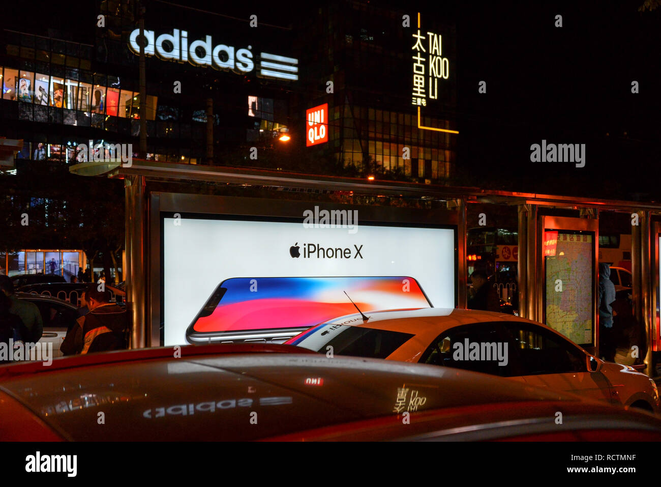 Peking, China - November 11, 2017: Night Shot in Sanlitun, einer geschäftigen Einkaufsstraße, mit Reklametafeln ad für die Freigabe, wenn das iPhone X. Adidas und Uniq Stockfoto