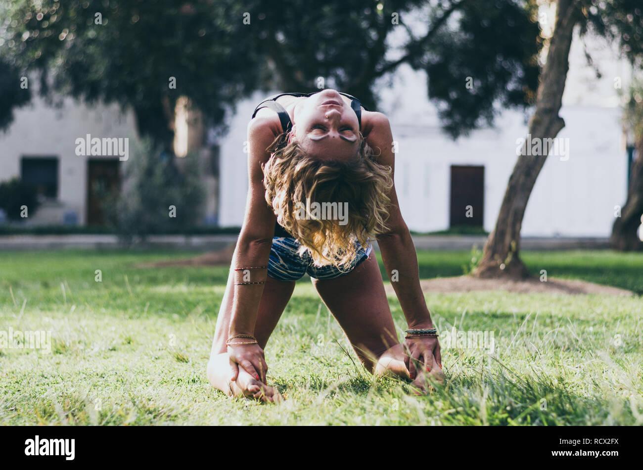 Yoga - draußen junge Schöne schlanke Frau Yoga Lehrer tun Kamel Ustrasana asana Übung im Freien dar. Vintage Retro wirksam gefiltert Hipster style Bild. Stockfoto