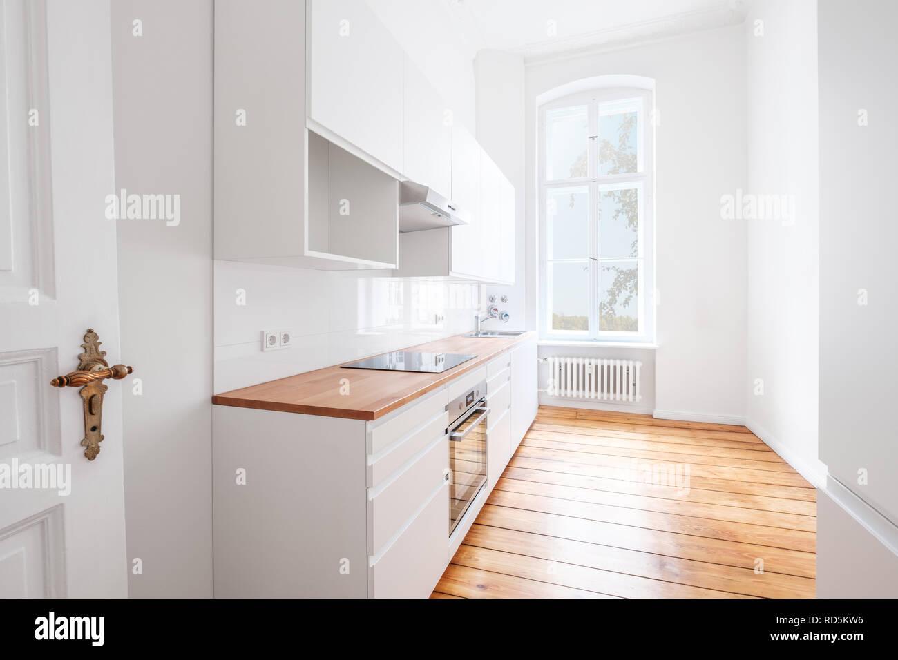 Leere, neue, integrierte Küche mit weißen Möbeln und ...
