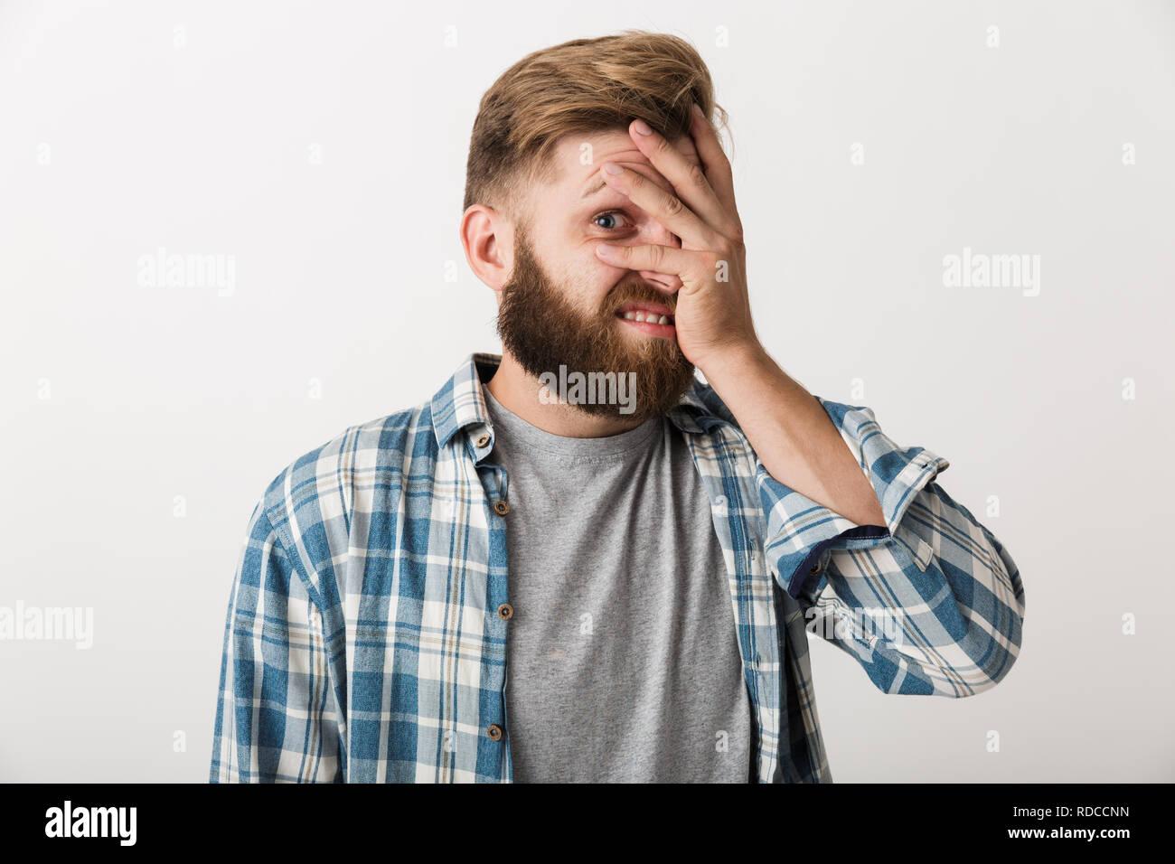 Beschämt, bärtigen Mann in Plaid Shirt auf weißem Hintergrund gekleidet, Abdeckung zeigen Stockbild