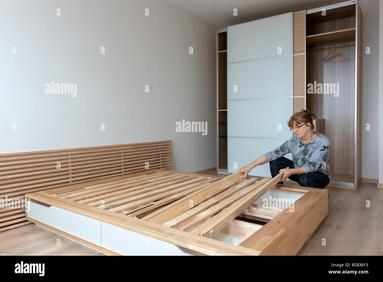 Ältere Frau ihre brandneue IKEA Bett aus Holz Montage in neu ...