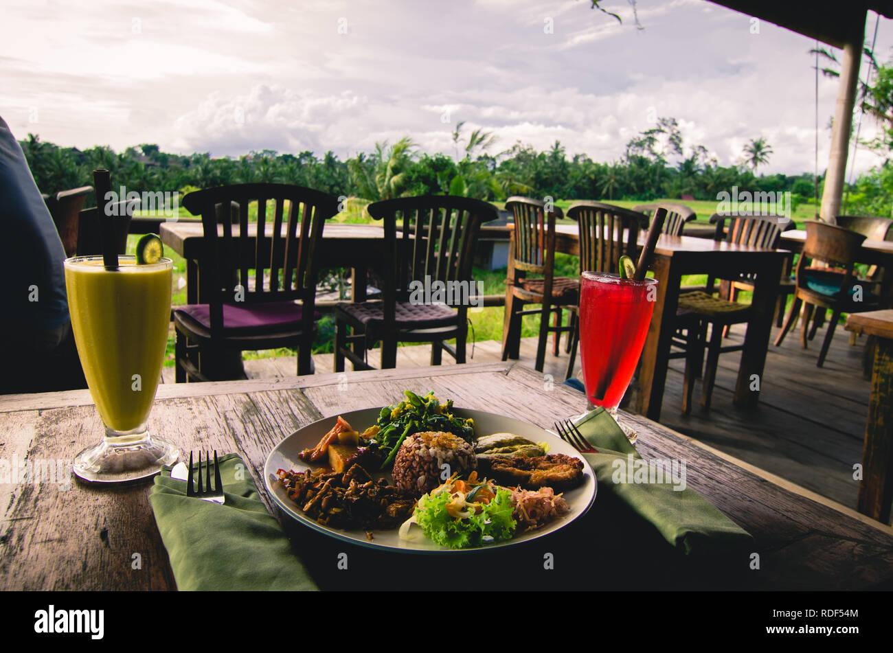 In einem traditionellen balinesischen Abendessen mit Blick auf die Reisfelder und den Regenwald Stockbild