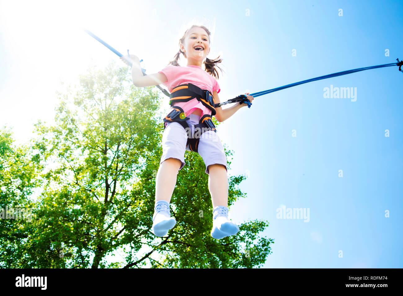 Kleines Mädchen springt hoch in die Luft mit einem Bungee Trampolin. Stockbild
