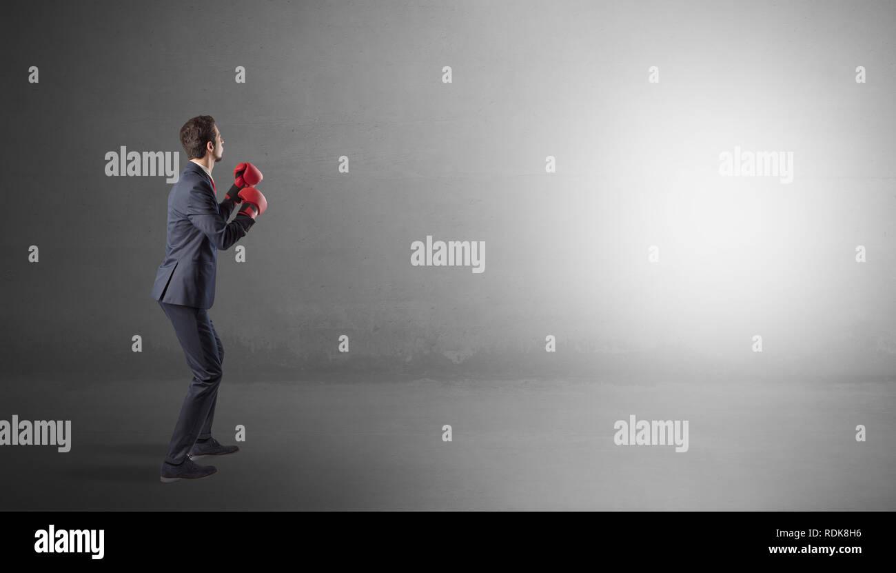 Unternehmer kämpfen mit Boxhandschuhen im leeren Raum Stockbild