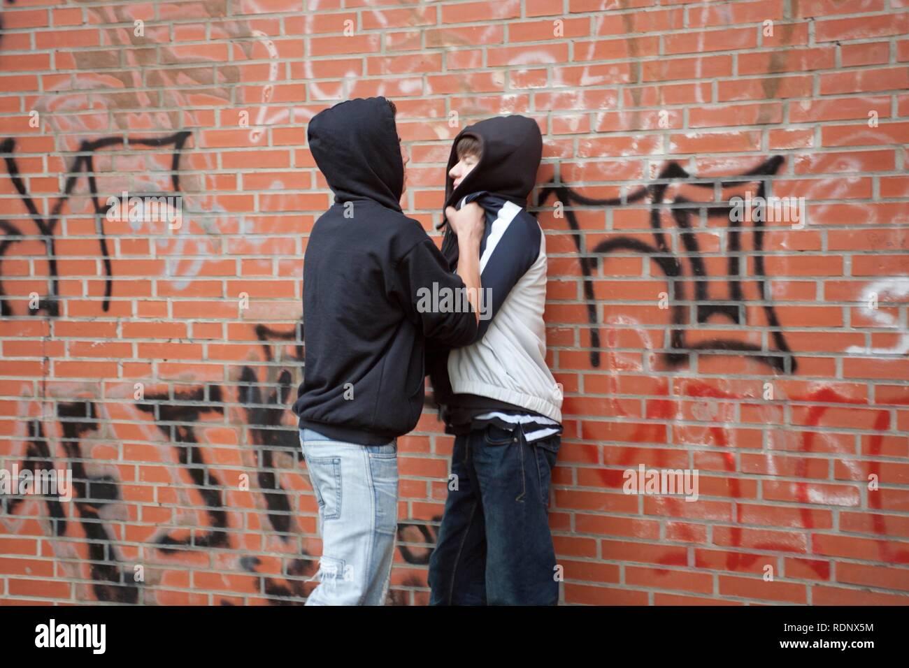 Teenager Schieben eines kleineren Jungen heftig gegen die Wand warf Szene Stockbild