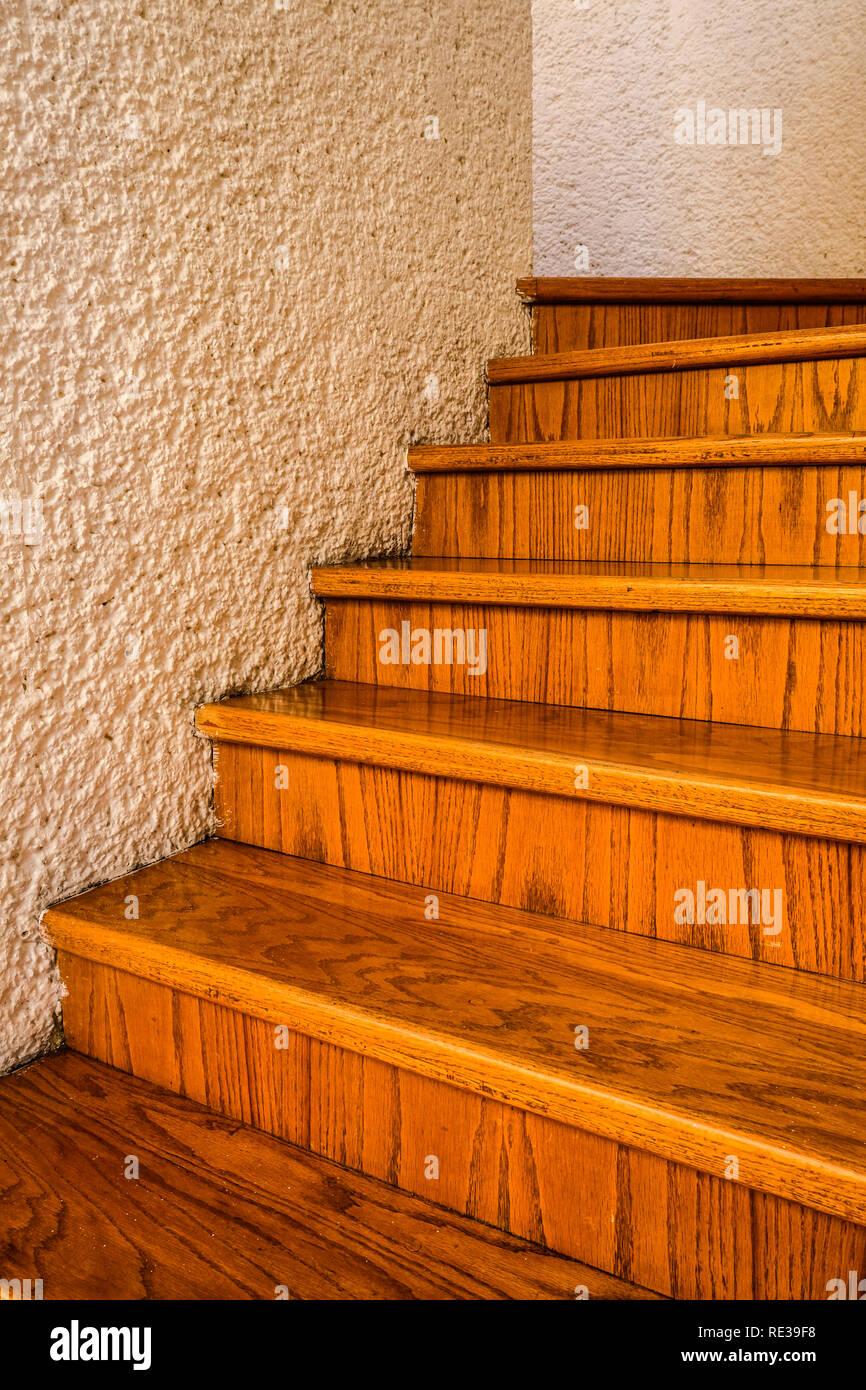 Eine gewundene Holztreppe zwischen weißen Wänden in einem Haus Stockbild