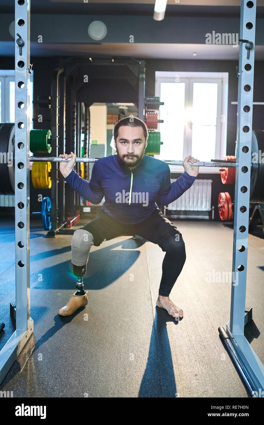 Porträt der jungen Sportler mit künstlichen Bein arbeiten mit Langhantel im Fitnessstudio Stockbild