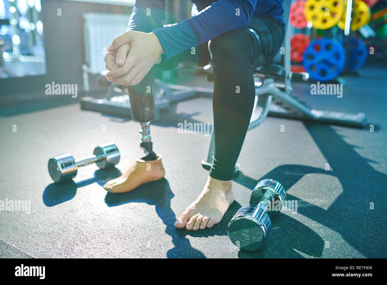 Nahaufnahme der unkenntlich Mann mit Prothese sitzt im modernen Fitnessraum und ruhephase zwischen Übungen mit Hanteln Stockbild