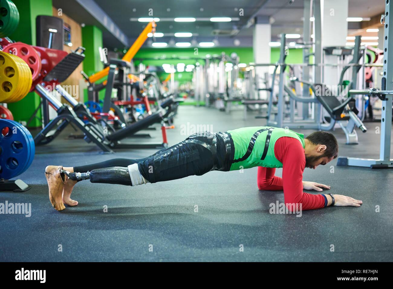 Konzentrierter junger bärtiger Mann mit beinprothese Durchführung plank Übung in modern mit Trainingsgeräten ausgestattet Stockbild