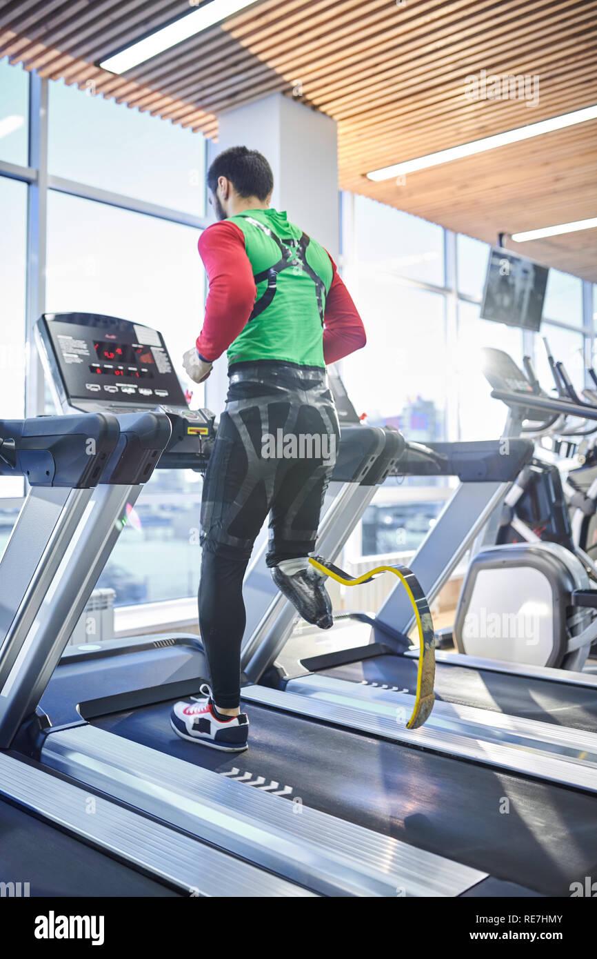 Ansicht der Rückseite des jungen behinderten Mann mit Fitness Beinprothese laufen auf Laufband, während allein die Ausbildung in modernen Fitnessraum Stockbild