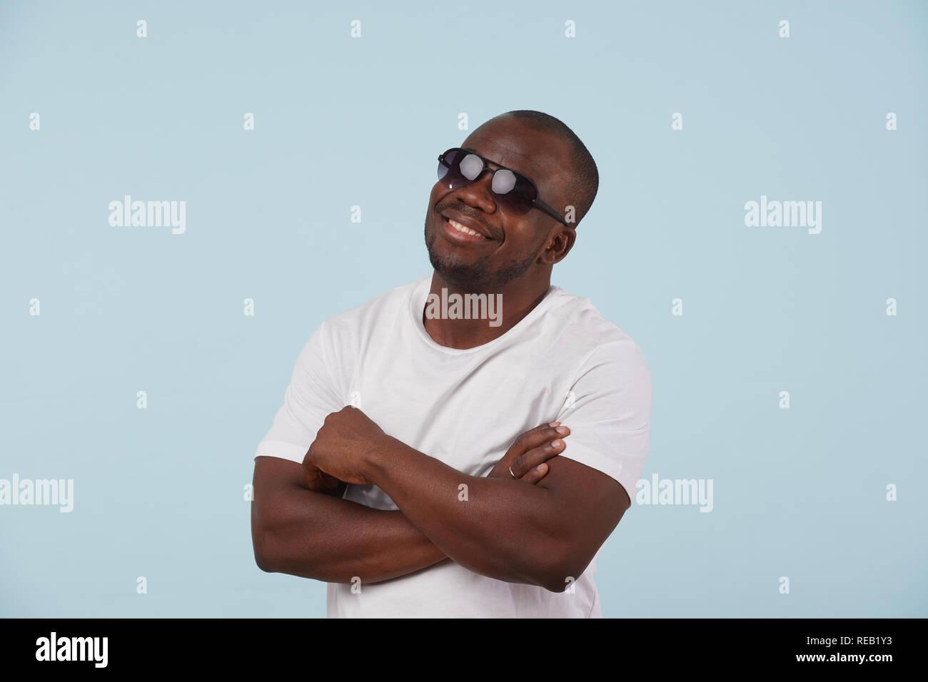 70ca98f0e01ad8 Lächelnd schwarzer Mann im weißen T-Shirt und Sonnenbrille schaut in die  Kamera vor hellblauem Hintergrund. Fett