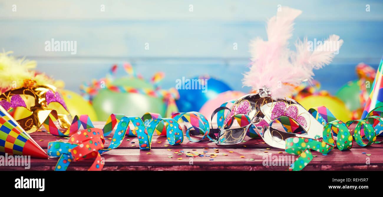 Bunte Karneval panorama Banner mit einem Wust von Party Ballone, Luftschlangen, konischen Hüten und Konfetti auf einem Holztisch mit Kopie Raum Stockfoto