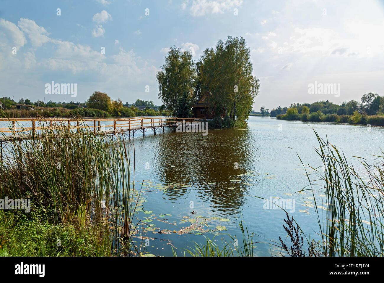 Kleines Haus der Insel. Landschaft mit Brücke zum Haus am See. Die ...