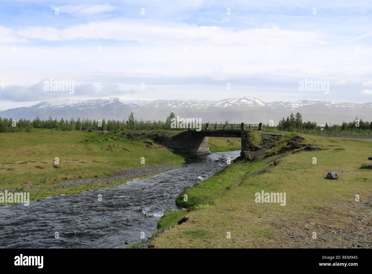 Brücke über Fluss mit Schnee und Bergen im Hintergrund in Island Stockbild