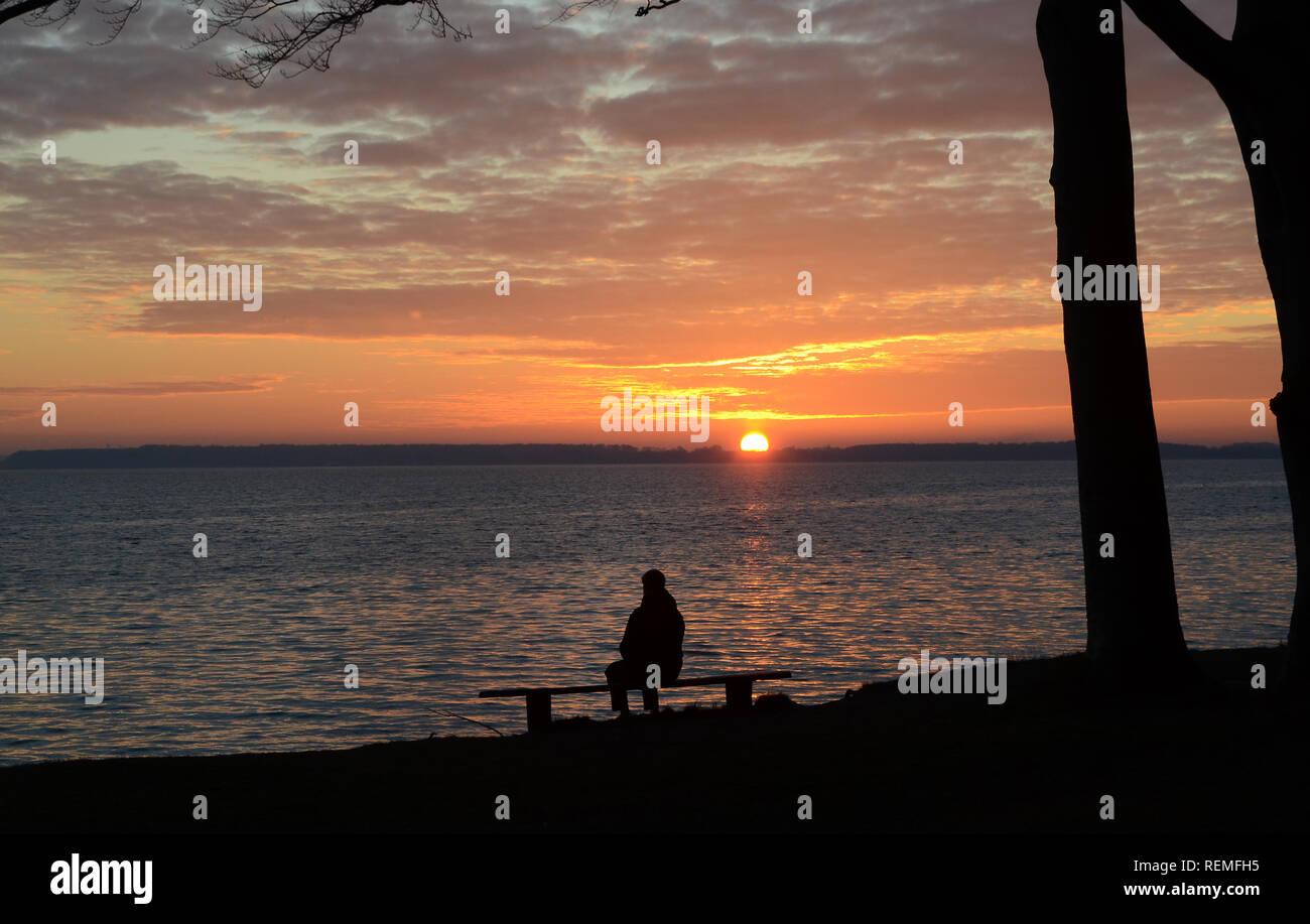 Landschaft mit Silhouette einer Person auf einer Bank sitzen, den Sonnenuntergang und altocumulus Wolken über dem Meer.. Stockbild