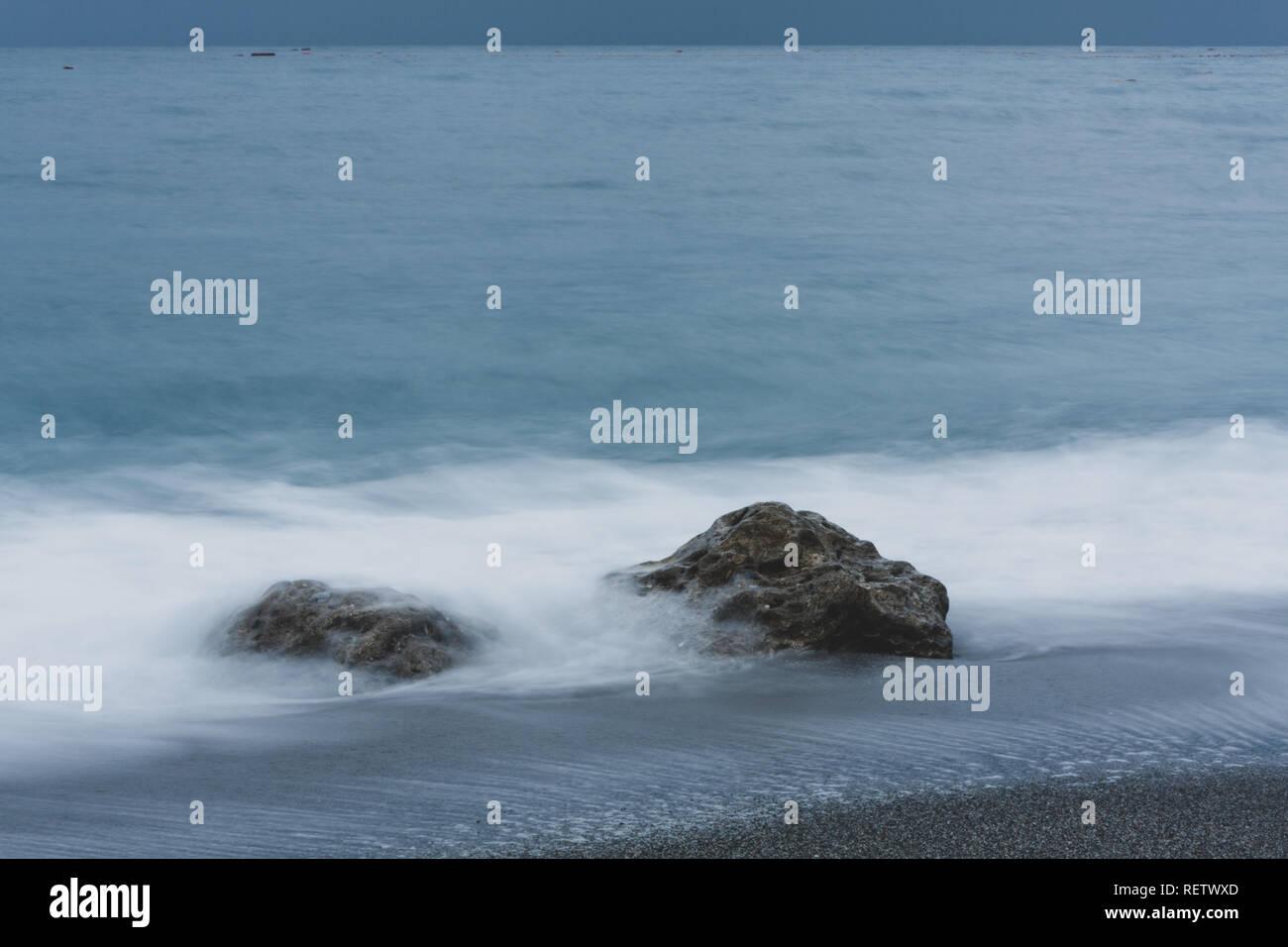 Ankommende Wellen rund um rock Absturz auf Strand, der in der Kamera blur Motion, abstrakten Hintergrund, Langzeitbelichtung, Hualien, Taiwan Stockfoto