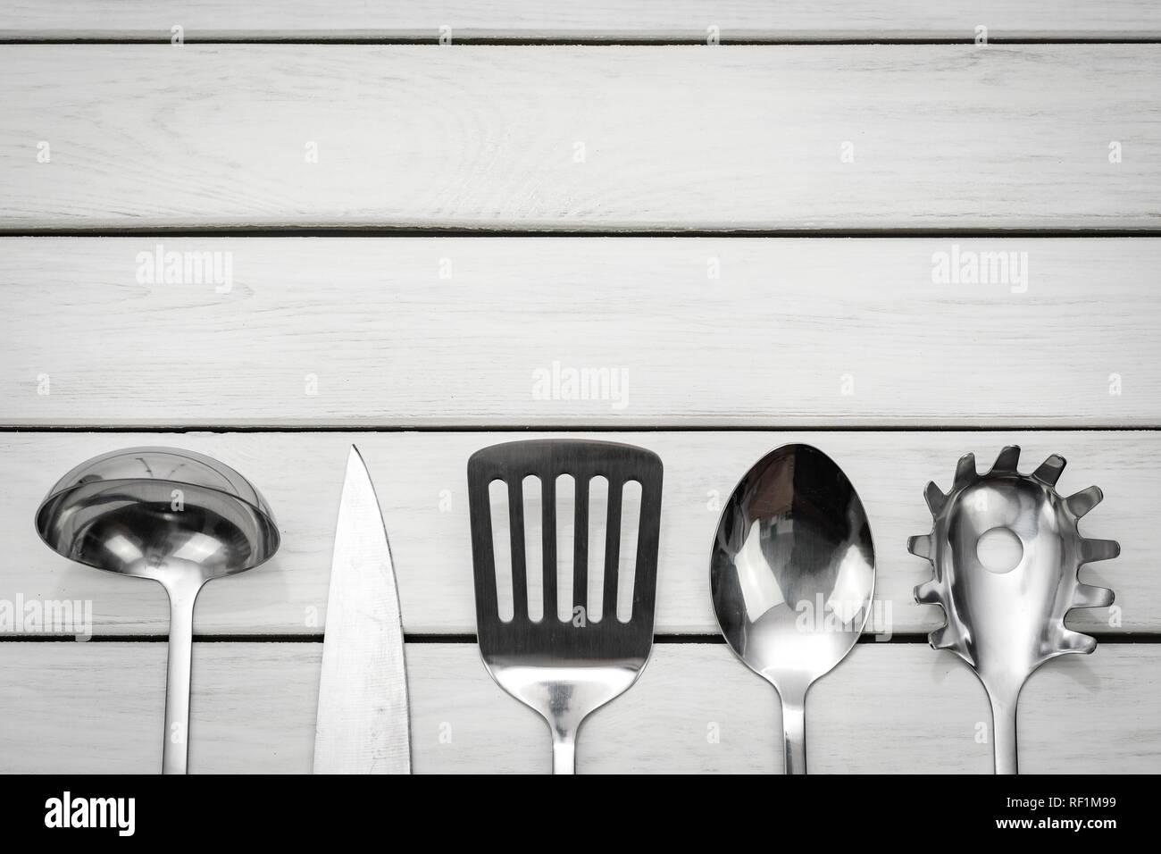 Ansicht von oben eine silberne Küchengeräte Collection auf einem Holztisch mit kopieren. Stockbild