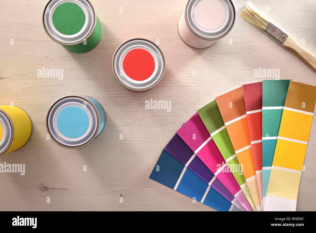 Farbige Lacke und Farben auf weißem Tabelle für die Renovierung der Materialien. Ansicht von oben. Horizontale Komposition. Stockfoto