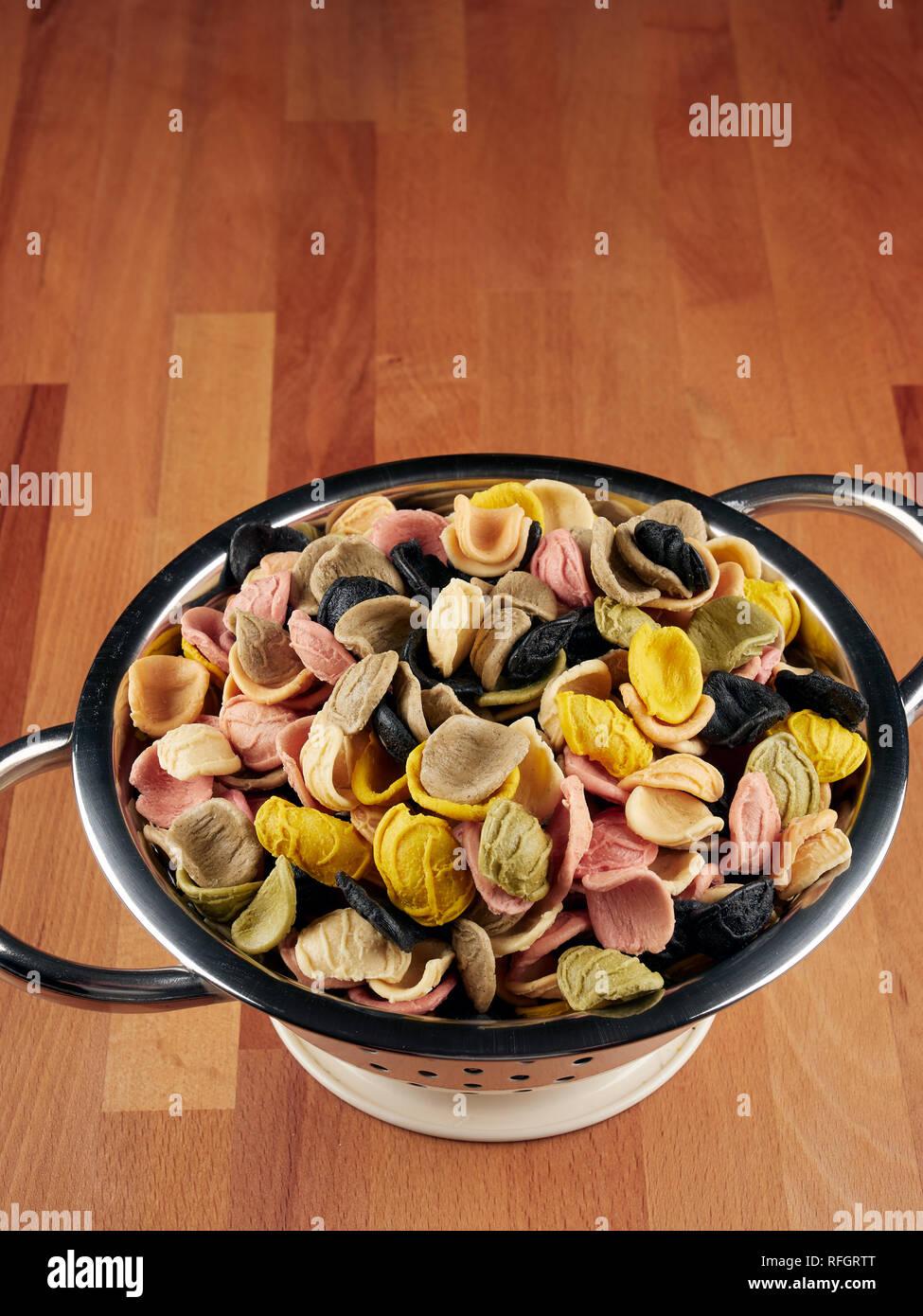 Bunte ungekocht orecchiette Pasta in einem kleinen Sieb Stockfoto