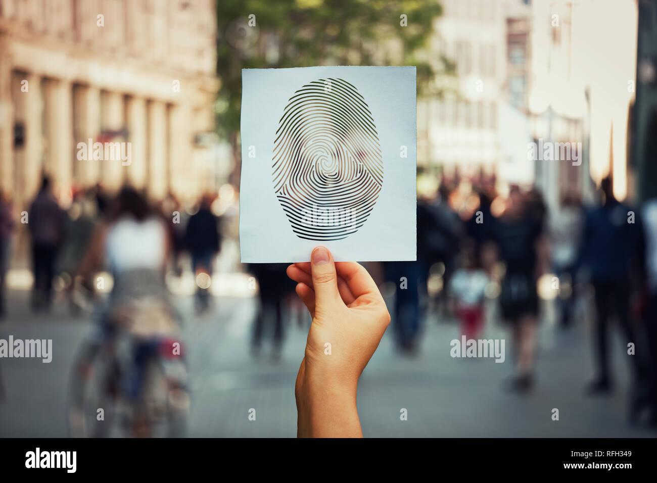 Hand hält ein Blatt Papier mit Fingerabdruck Symbol auf einer belebten Straße Hintergrund. Konzept der sozialen Identität und Privatsphäre. Persönliche private Daten diver Stockbild