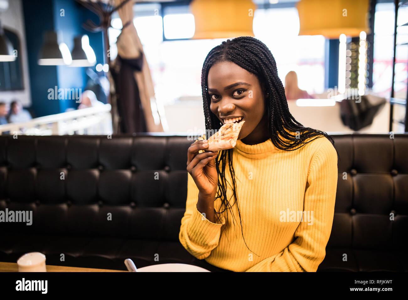 Junge afrikanische amerikanische Frau essen Pizza im Cafe Stockfoto