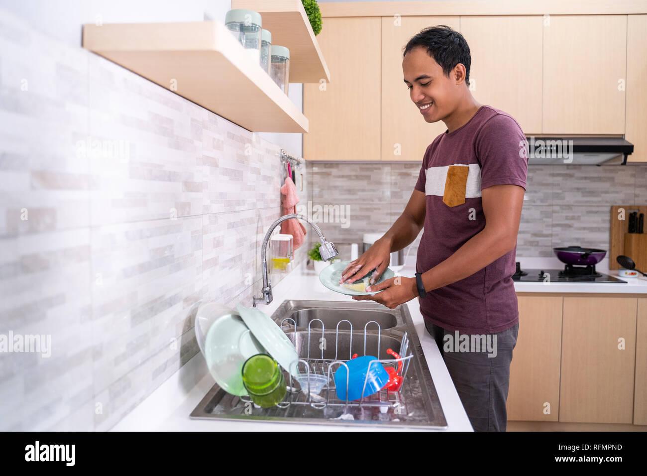 Waschen mann Teller in die Spüle Stockfoto