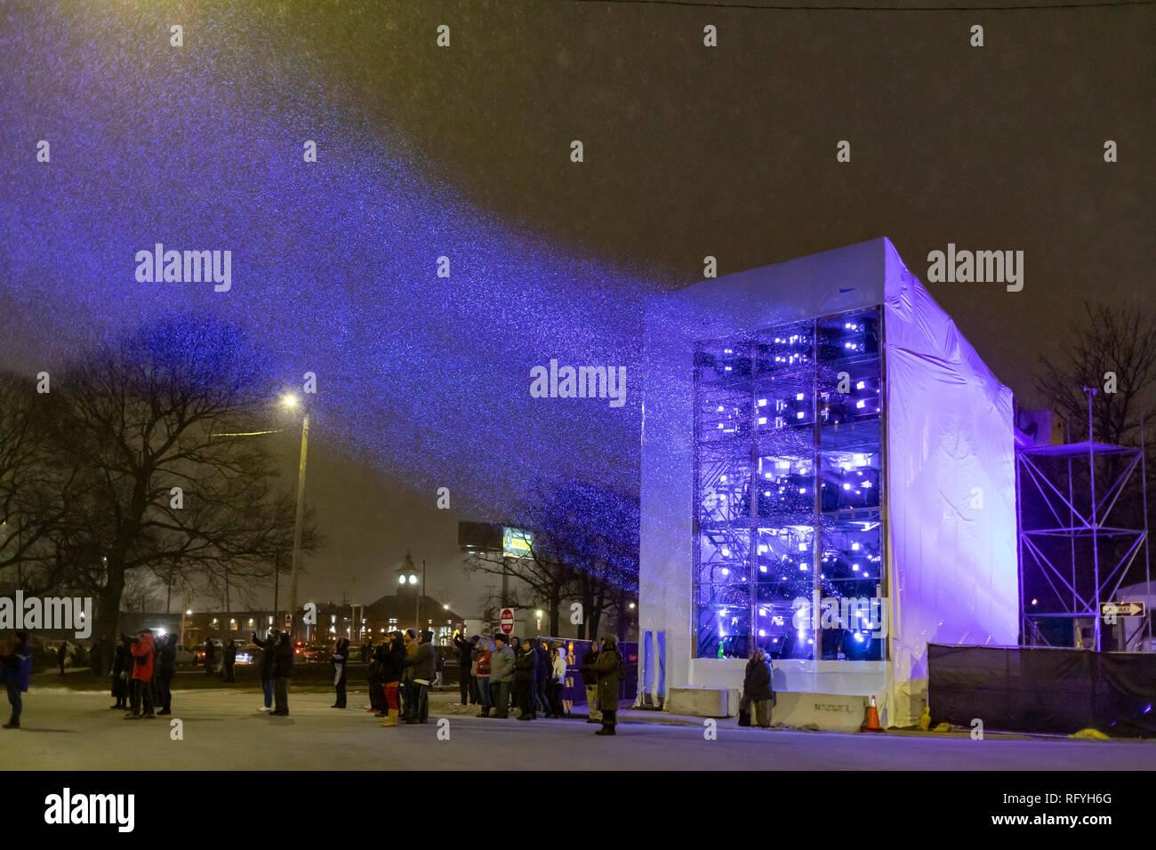 Detroit, Michigan - Menschen während eines Schneesturms wie Ford Motor Company projiziert eine Lichtshow auf die Michigan Central Railroad Station als Teil o beobachtete Stockbild
