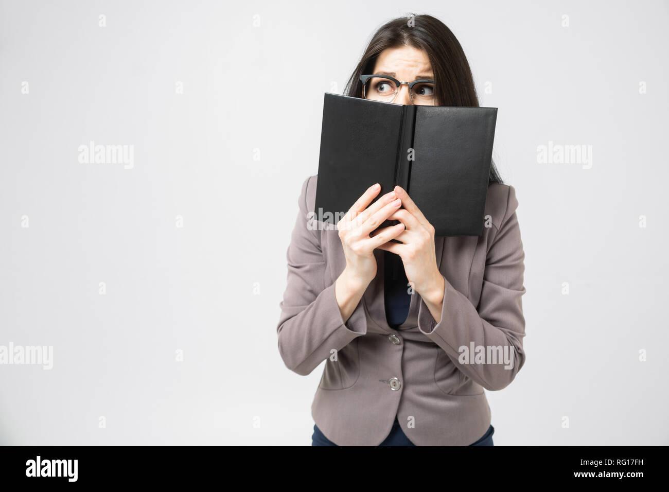 Junge Brünette den Boden ihr Gesicht mit einem Tagebuch auf weißem Hintergrund Stockbild