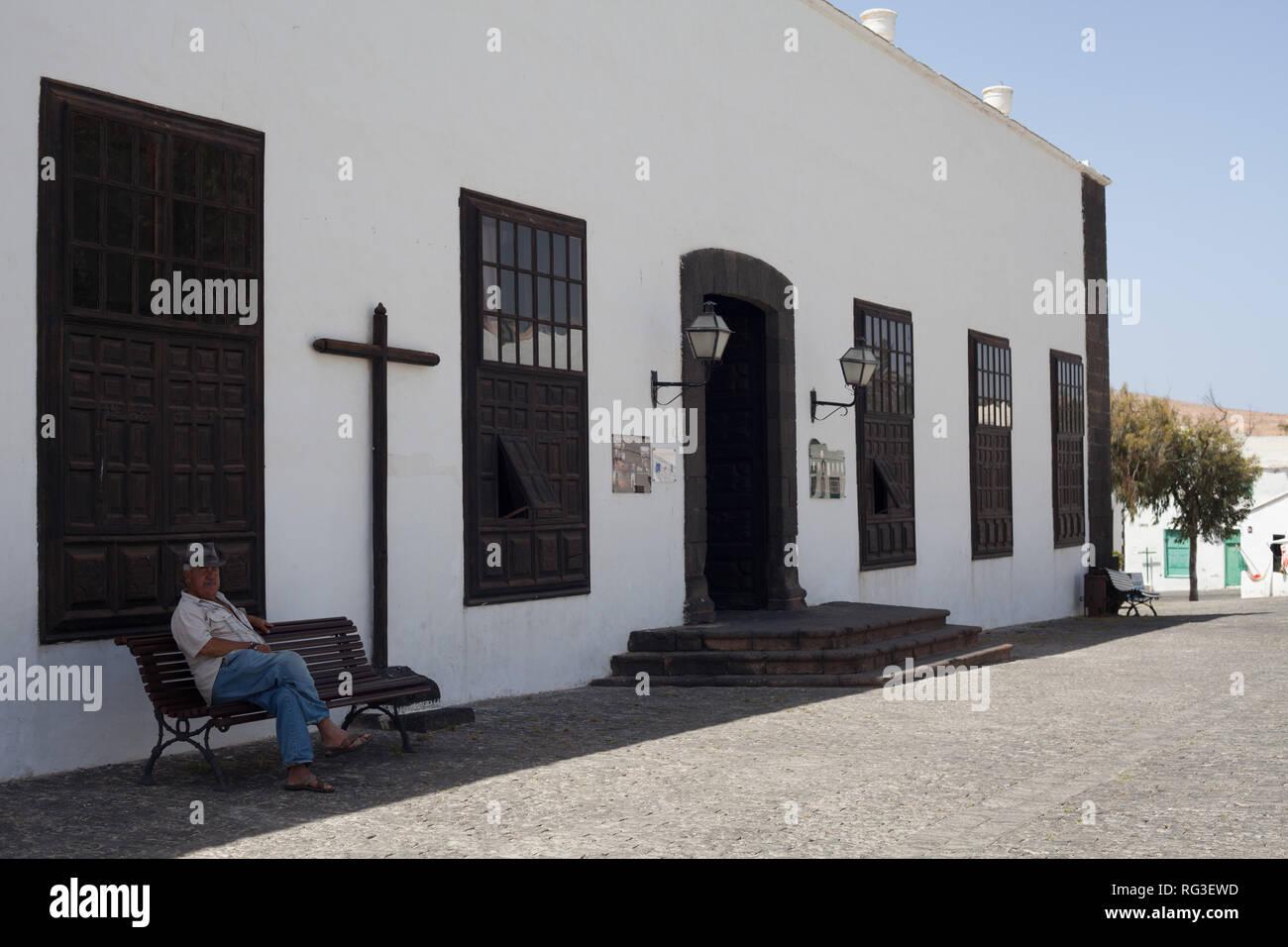Lokaler Mann auf einer Bank ausserhalb Museo del Timple (iconic String Instrument der Kanarischen Inseln), Plaza de la Constitucion, eguise, Lanzarote, Spanien sitzen Stockbild