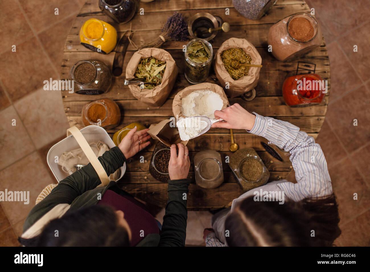 Hohe Betrachtungswinkel von Shop putting Mehl in Papiertüte für Kunden Assistent an Null Abfall Shop. Ansicht von oben. Stockfoto