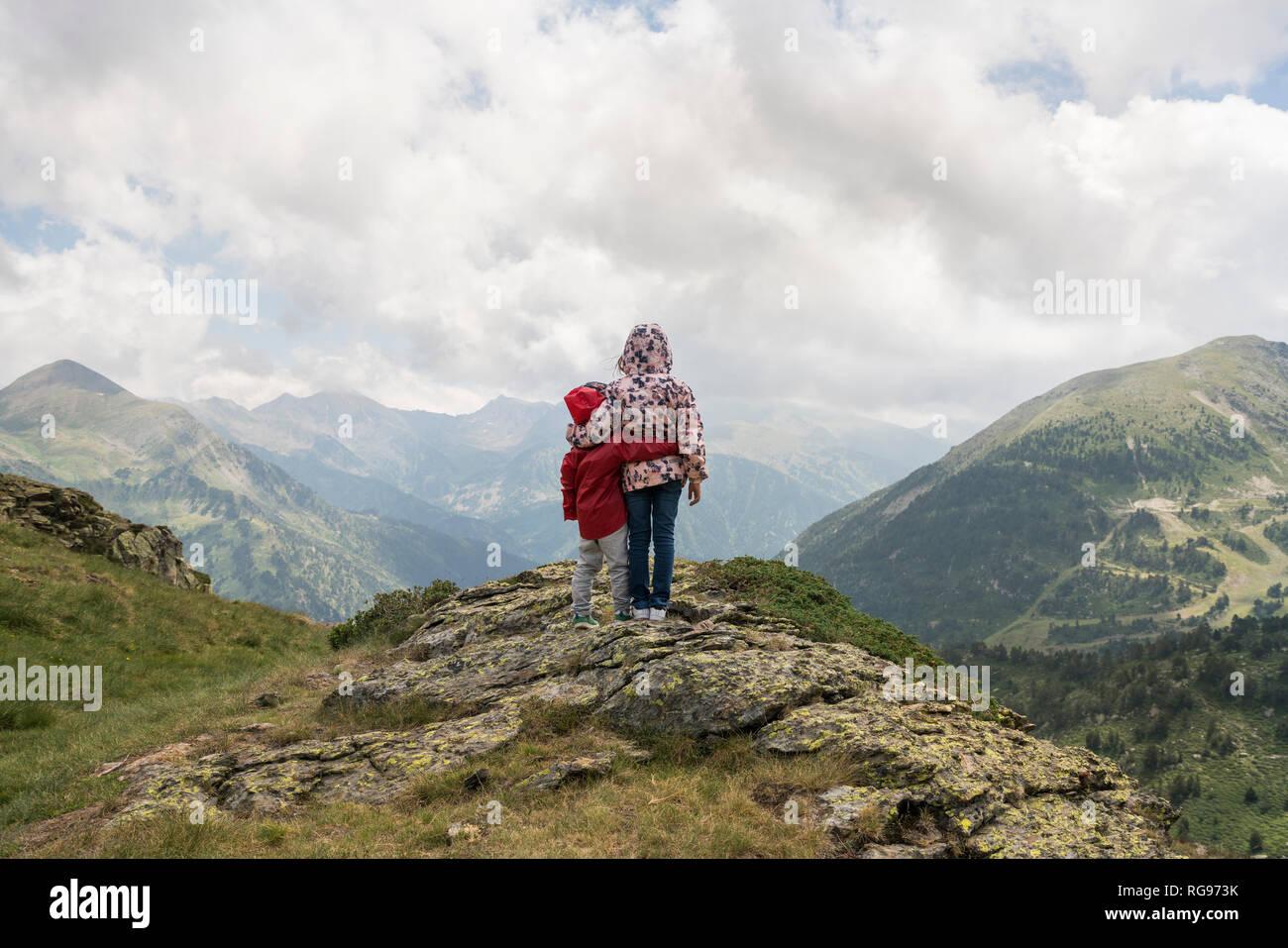 Andorra, Ordino, junges Mädchen und ihr Bruder, um den Arm, stehend auf Sicht in die Berge Stockfoto
