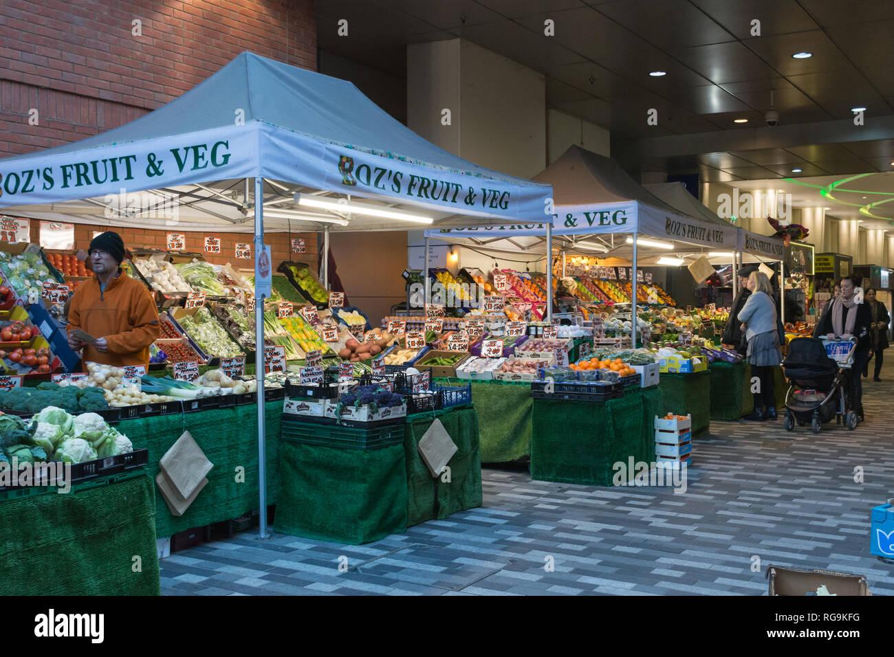 Obst und Gemüse Marktstände auf dem Markt zu Fuß in das Stadtzentrum von Woking, Surrey, UK, mit Leute einkaufen. Alltag. Stockbild