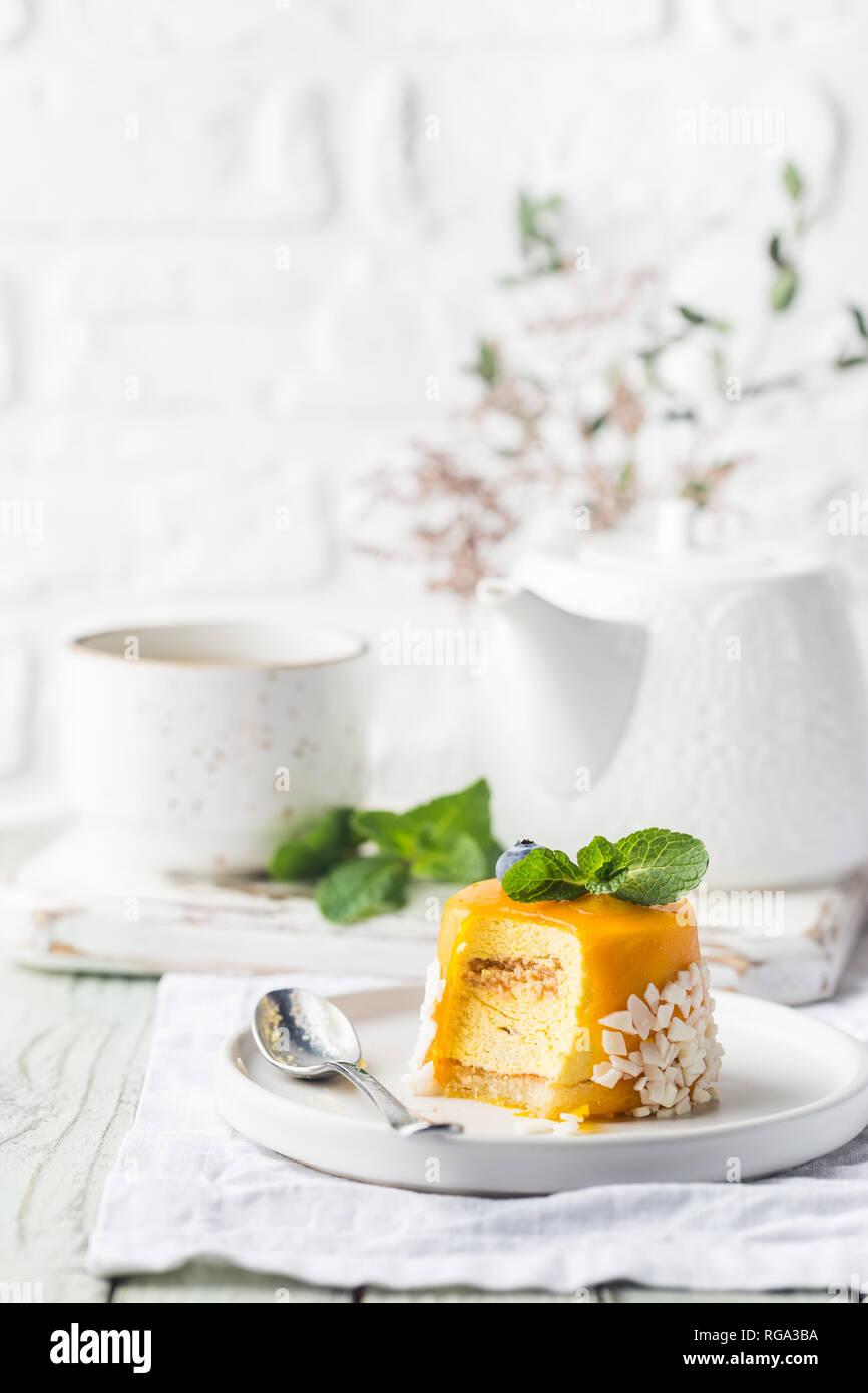 Stück mango Mousse Torte auf dem Teller über weiße Holztisch ...