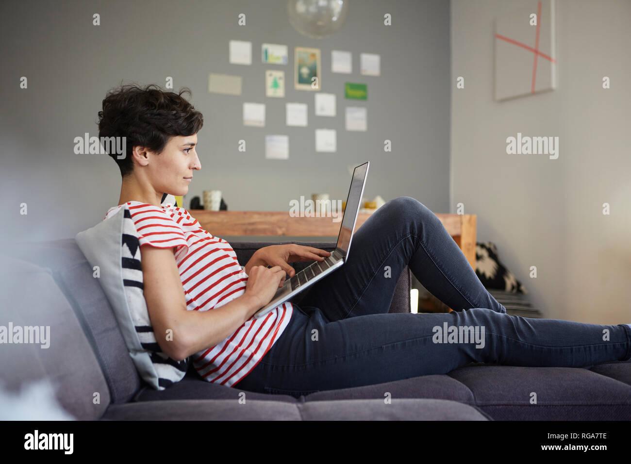 Frau mit Laptop auf der Couch zu Hause Stockbild