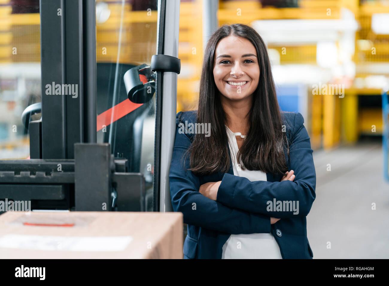 Selbstbewusste Frau im Logistikzentrum, mit verschränkten Armen Stockfoto