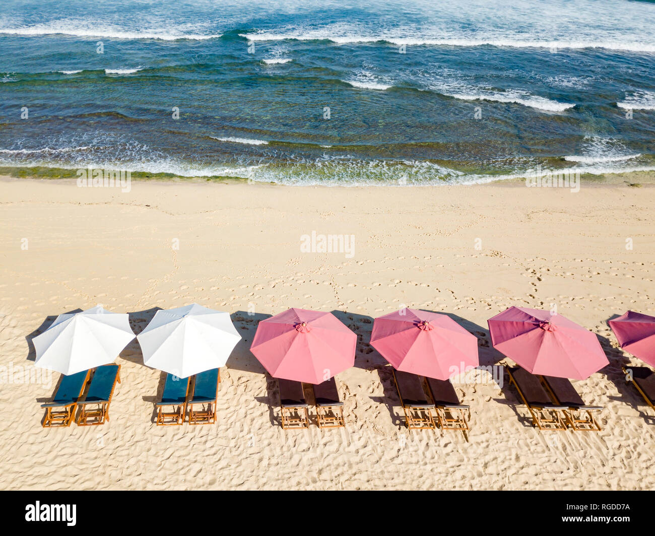 Indonesien, Bali, Luftaufnahme von Balangan Beach, Sonnenliegen und Sonnenschirmen Stockbild