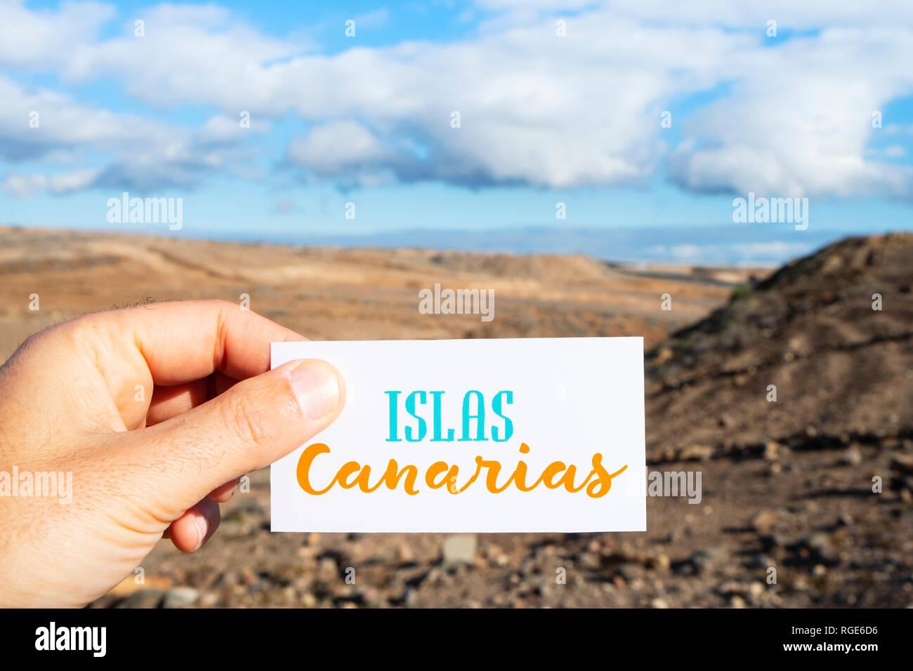 Nahaufnahme der Hand eines kaukasischen Mann hält ein Schild mit dem Text Islas Canarias Kanarische Inseln auf Spanisch geschrieben, vor einem trockenen landscap Stockbild