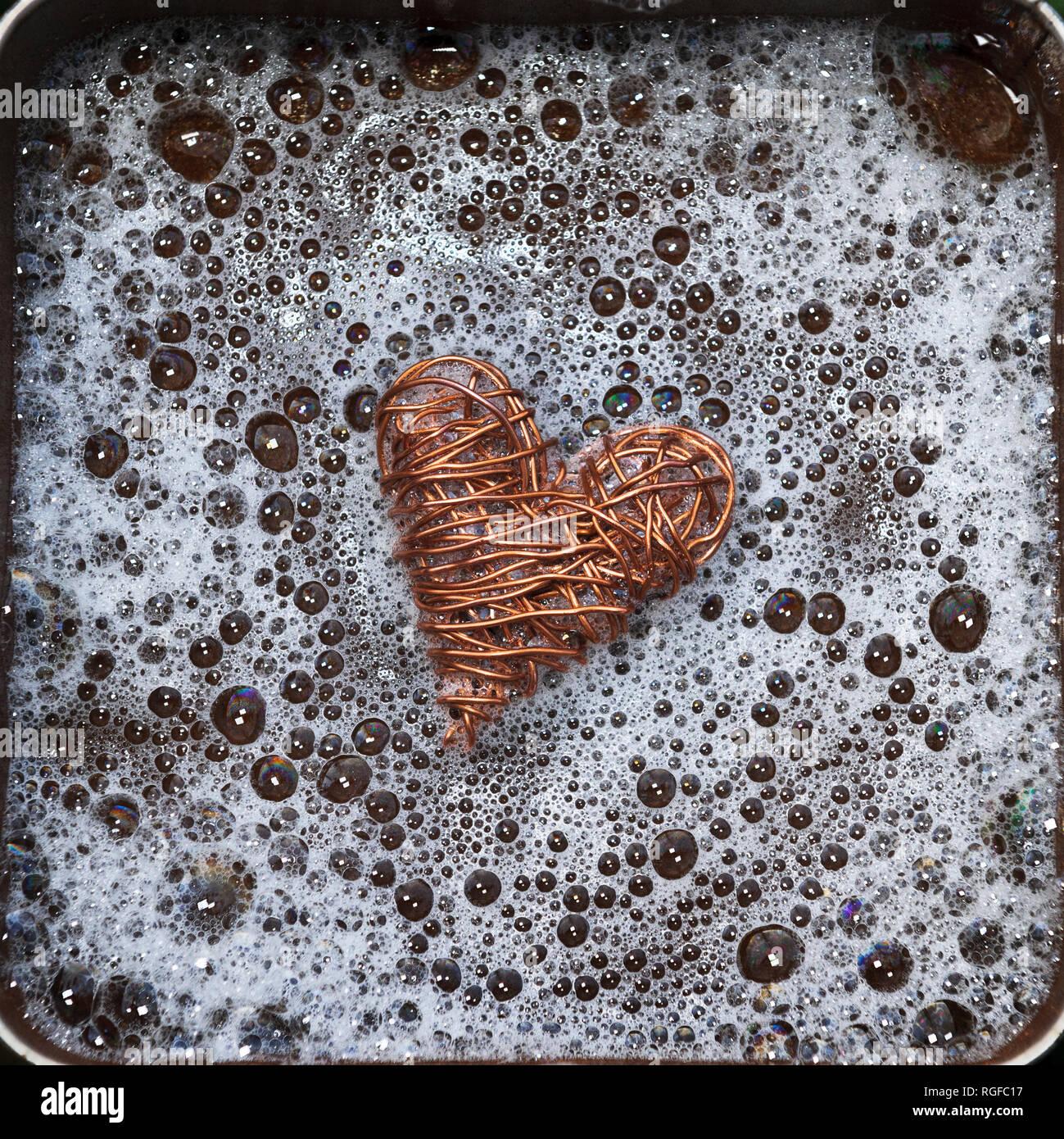 Herz aus Kupferdraht von sprudelndem Wasser umgeben. Stockbild
