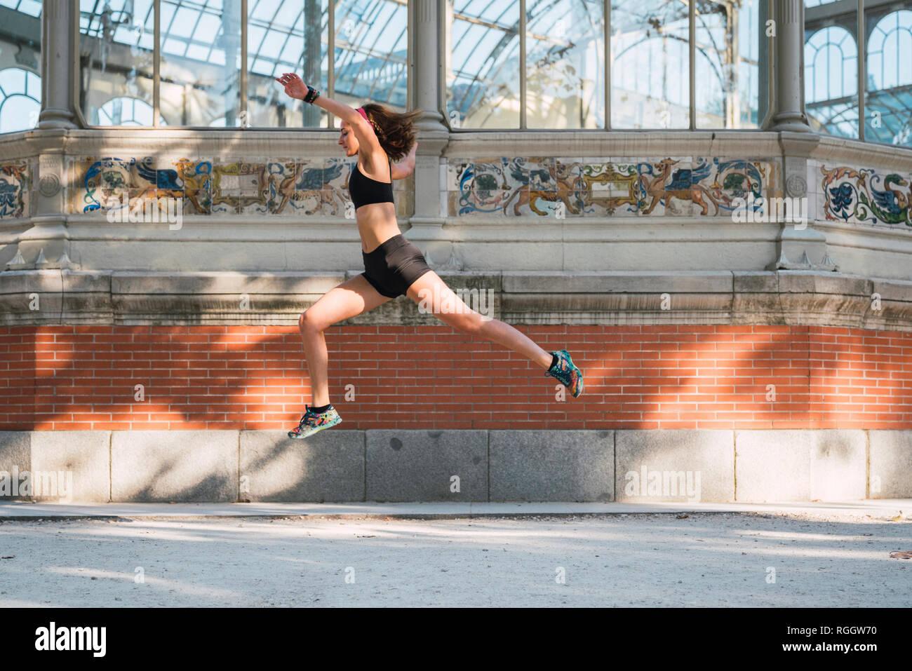 Passen junge Frau läuft ein Springen in Park Stockfoto