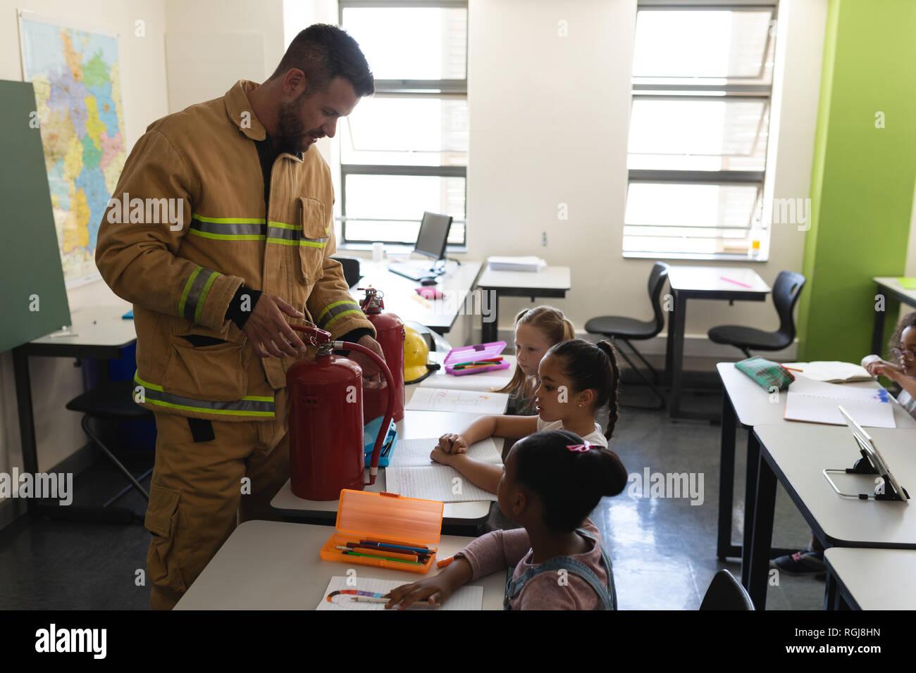 Seitenansicht der männlichen Kaukasier Feuerwehrmann Lehre schoolkids über Brandschutz, Feuerlöscher in Klassenzimmer der Volksschule Stockfoto