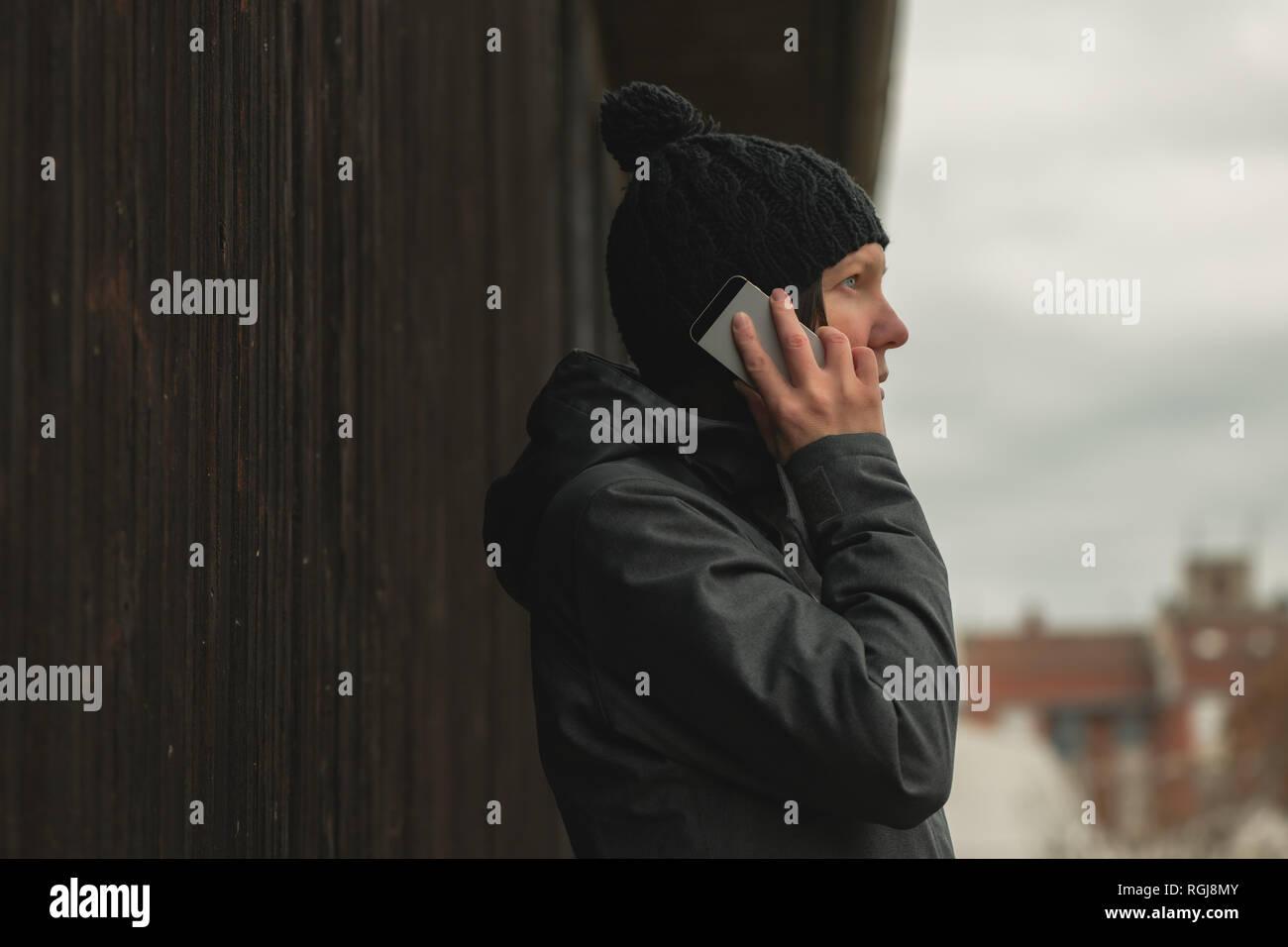 Besorgt Frau Gespräch am Handy auf der Straße in der Kälte des Winters Tag Stockfoto